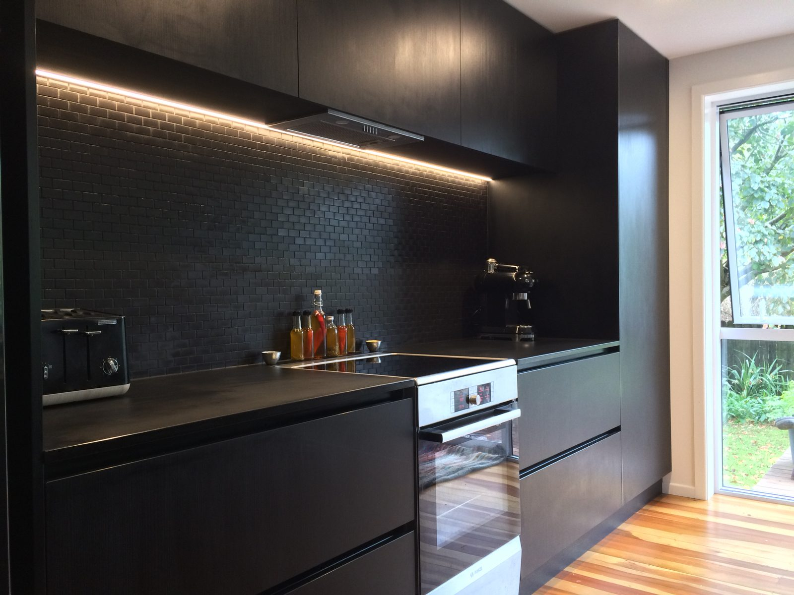 black kitchen with wooden floors